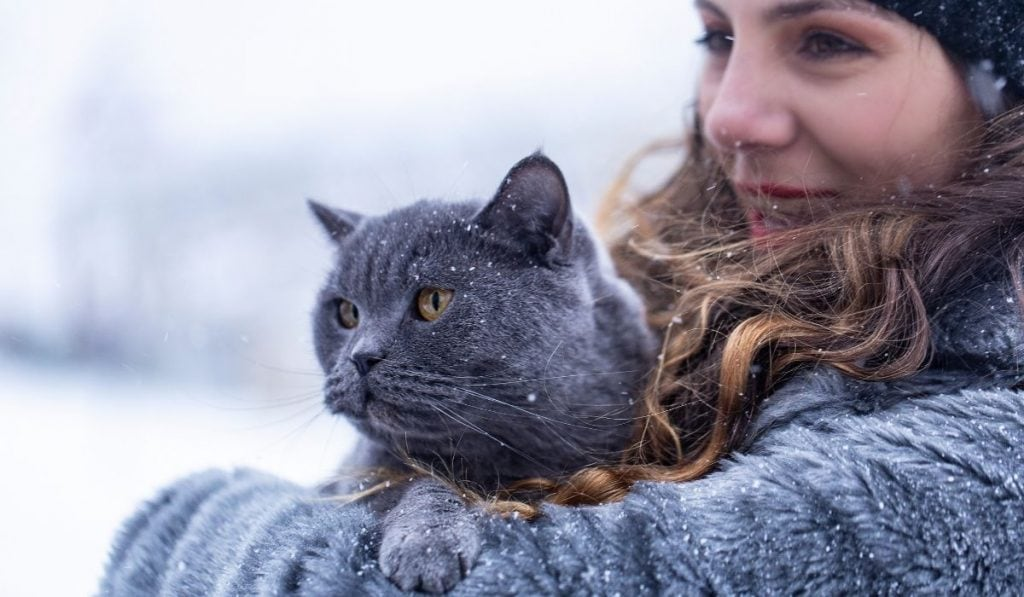 a girl carrying her cat outside in the snow