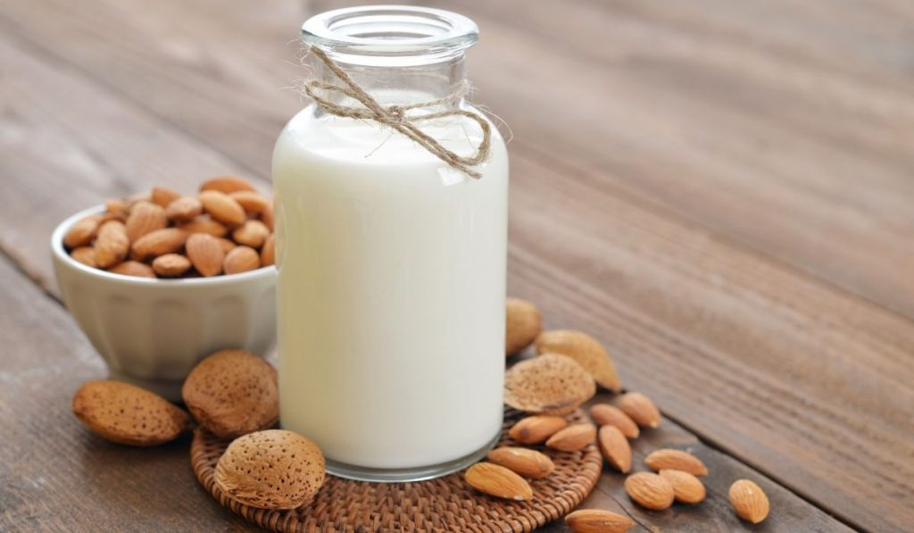 almond milk in a cute small jug with some almond nuts in the background