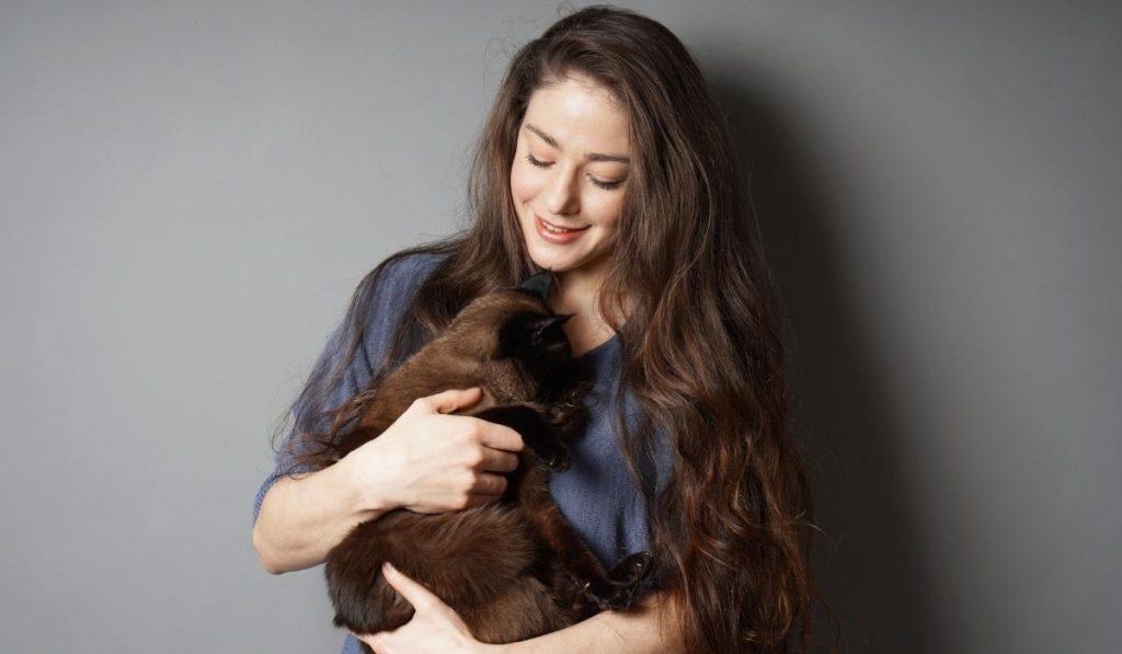 woman cuddling her cat