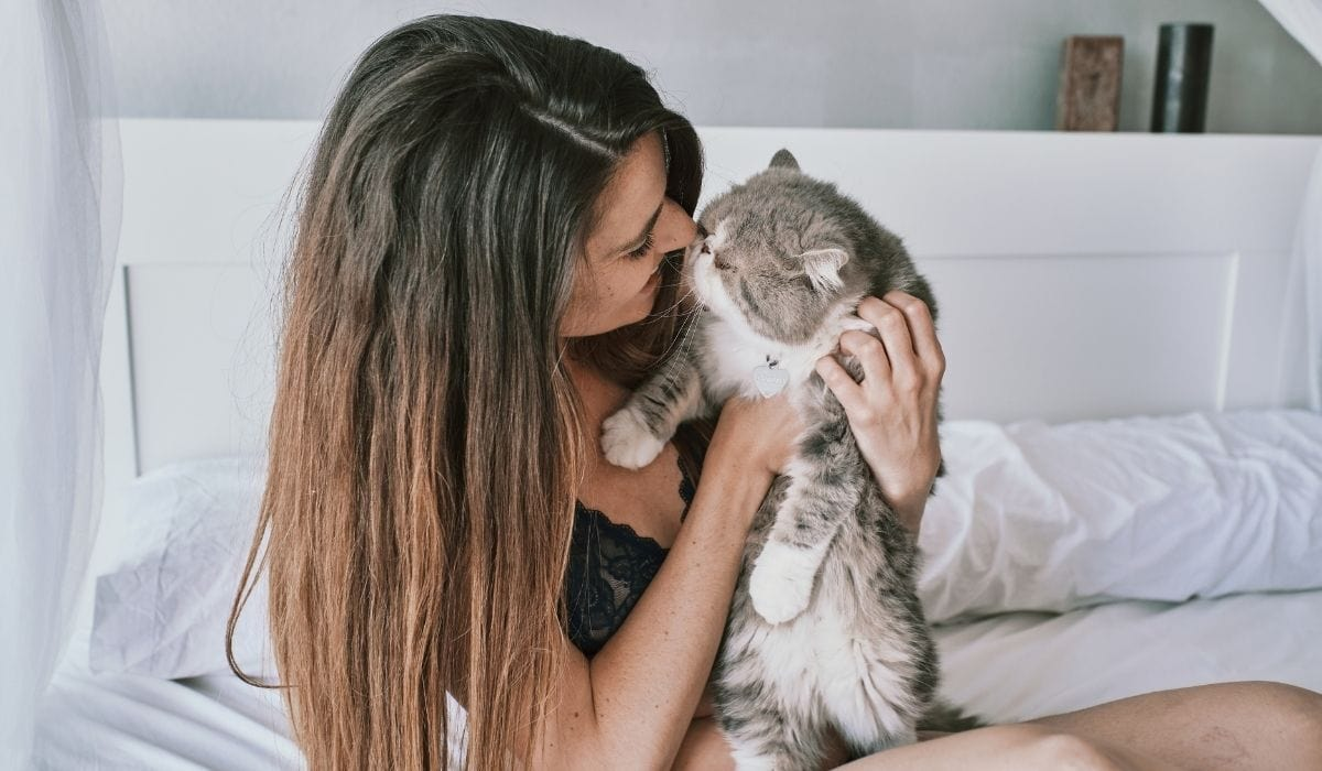 woman cuddling with her cute cat
