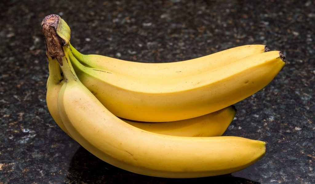 A bunch of bananas on marble like tile
