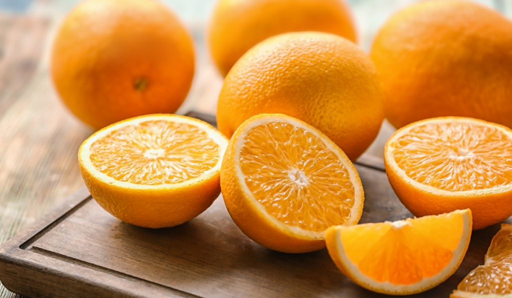Slices of oranges with unsliced oranges on the background