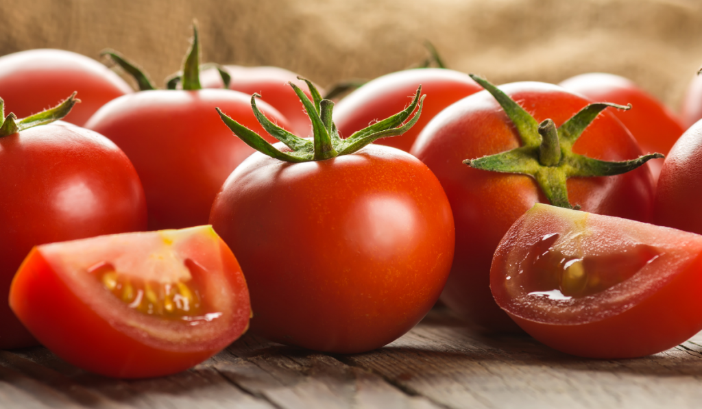 Two slices of tomato with unsliced on the background