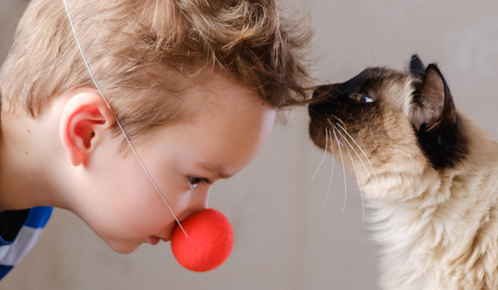 A boy with red nose toy and a kit kissing his forehead.