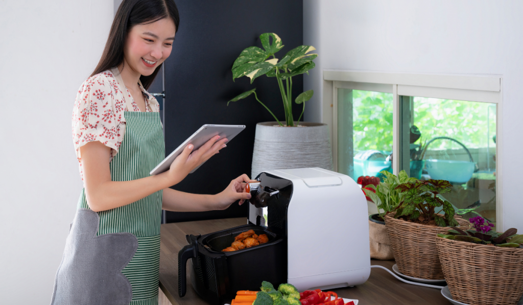 A girl cooking using the air fryer in the kitchen.